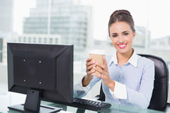Smiling brunette businesswoman holding disposable cup Stock Images