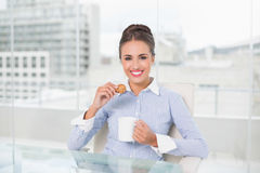 Smiling brunette businesswoman holding mug and cookie Stock Image