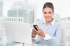 Smiling brunette businesswoman holding smartphone Stock Images