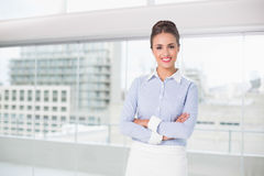 Smiling brunette businesswoman standing with arms crossed Stock Photo