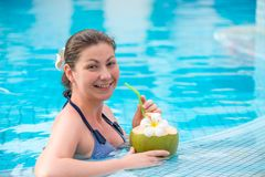 Smiling brunette with a coconut resting in a pool Royalty Free Stock Images