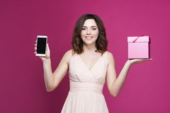 Smiling brunette in a dress is holding a phone and a gift box stock images