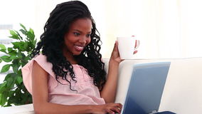 Smiling brunette drinking a coffee in front of her laptop Stock Images