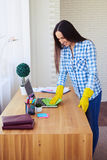 Smiling brunette dusting laptop standing on table Royalty Free Stock Photography