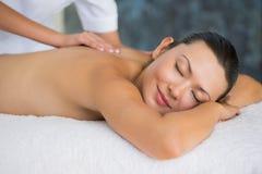 Smiling brunette enjoying a back massage Royalty Free Stock Photo