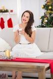 Smiling brunette enjoying a hot beverage at christmas Royalty Free Stock Photo