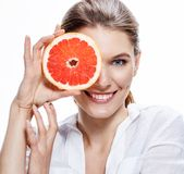 Smiling brunette european woman with mottled orange slice - isolated on white background Royalty Free Stock Photo
