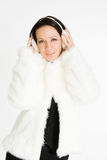 Smiling brunette in furry headphones. Picture of smiling brunette in furry headphones and coat royalty free stock photography