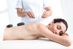 Smiling brunette getting hot stone massage Stock Photos