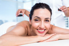 Smiling brunette getting hot stone massage Royalty Free Stock Image