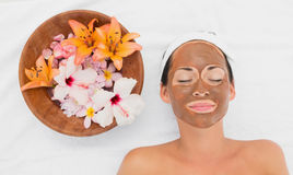 Smiling brunette getting a mud treatment facial beside bowl of flowers Stock Photo