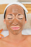 Smiling brunette getting a mud treatment facial Royalty Free Stock Photos