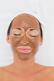 Smiling brunette getting a mud treatment facial Stock Photography