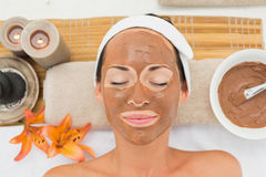 Smiling brunette getting a mud treatment facial Royalty Free Stock Image