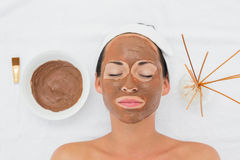 Smiling brunette getting a mud treatment facial Stock Image