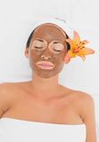 Smiling brunette getting a mud treatment facial Royalty Free Stock Photography