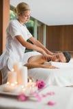 Smiling brunette getting a shoulder massage Stock Photo
