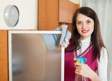Smiling brunette girl cleaning  glass Stock Photo