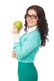 Smiling brunette girl in green skirt and blouse holding apple Stock Photos