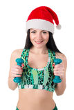Smiling brunette girl in the hat of Santa Claus doing exercises with dumbbells. Stock Photos