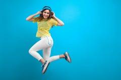 Smiling brunette girl in headphones jumping Stock Photo