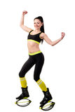 Smiling brunette girl in kangoo jumps shoes showing a muscles on Stock Images