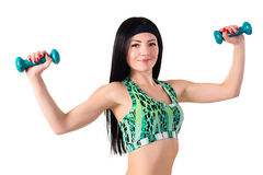 Smiling brunette girl with long hair holding a dumbbell Royalty Free Stock Photography