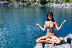Smiling brunette girl with long hair sitting on the rocks in the Royalty Free Stock Photography