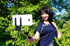 Smiling brunette girl makes selfie photos using phone and monopo Royalty Free Stock Images