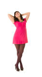Smiling brunette girl in pink dress posing Stock Image