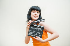 Smiling brunette girl showing clapper on white background Royalty Free Stock Photo