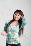 Smiling brunette girl with soap bubbles Stock Photos
