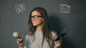 Brunette Looks at Globe and Passport. Smiling brunette in glasses looking at globe and passport with the ticket in the grey background with travel animation stock footage