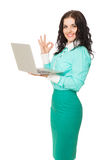 Smiling brunette in green skirt and blouse holding laptop showin Royalty Free Stock Images