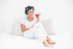 Smiling brunette in hair curlers sitting on her bed holding a co Stock Images