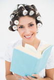 Smiling brunette in hair rollers holding a book on bed Royalty Free Stock Image