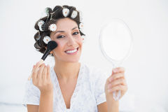 Smiling brunette in hair rollers holding hand mirror and applyin Royalty Free Stock Image