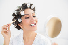 Smiling brunette in hair rollers looking in hand mirror and brus Stock Images