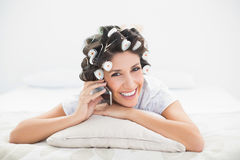 Smiling brunette in hair rollers lying on her bed making a phone call Stock Image