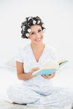 Smiling brunette in hair rollers reading a book on bed Royalty Free Stock Photos