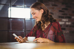 Smiling brunette having coffee and texting Stock Image