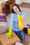 Smiling brunette having fun while cleaning Royalty Free Stock Images