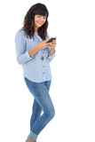 Smiling brunette with her mobile phone texting a message Royalty Free Stock Photography