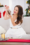 Smiling brunette holding  baby shoes at christmas Stock Photos