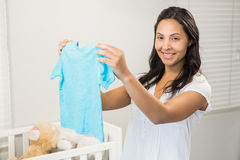 Smiling brunette holding baby tshirt Royalty Free Stock Photography