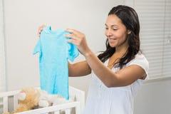 Smiling brunette holding baby tshirt Royalty Free Stock Image