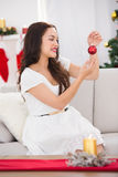 Smiling brunette holding a bauble at christmas Stock Photography