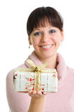 Smiling brunette holding christmas present. Young brunette holding christmas present - focus on present. Isolated over white Royalty Free Stock Image