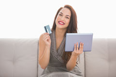 Smiling brunette holding credit card an tablet Royalty Free Stock Photo