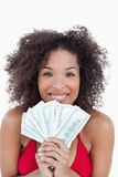 Smiling brunette holding a fan of bank notes Royalty Free Stock Photos